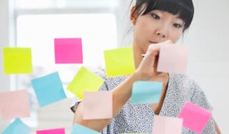 A woman makes notes on colorful Post-Its.