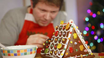 Young man preparing a gingerbread cookie house for his children at christmas time. Selective focus on house