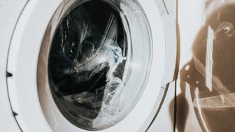 Close-up on a white washing machine with a glass front, as clothing spins around mid-cycle. The glass casts a shadow on the wall.