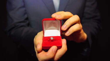 A closeup of an engagement ring in its velvet box.