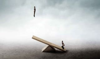 A man jumps onto a seesaw, propelling another man into the air.