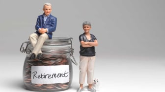 picture of dolls sitting on jar of retirement money