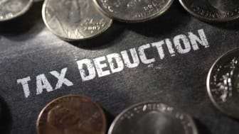 picture of tax deduction written on table surrounded by coins