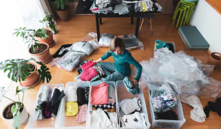 a woman organizes clothes in living room of her home.
