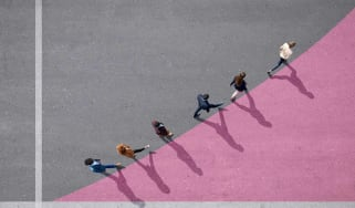 An aerial shot of a group of people walking in a line curving upward.