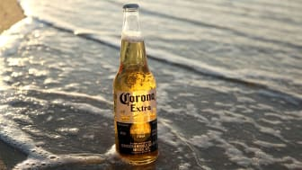 A Corona beer sitting on the beach at high tide