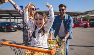 A little girl sits in a shopping cart pushed by her parents.