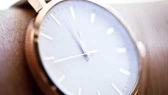 Close-up of a cream and rose gold wristwatch on a woman's arm showing a few minutes before 12 o'clock.