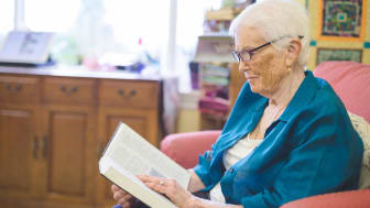 A woman reads a book in her nursing home room.