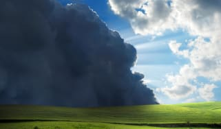 Storm clouds gather over a meadow.