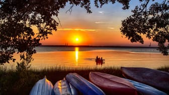 A North Carolina lake with a lone boater seen at sunset