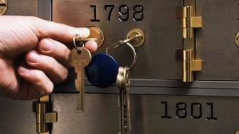 Person inserting key in safe deposit box, close-up