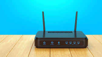 A black wireless router against a blue wall