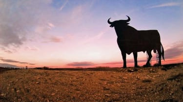 Landscape in Spain. A figure with the shape of a bull emerges in the sunset.