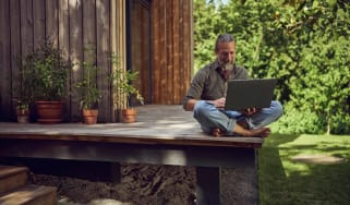 retired man sits on the porch of his tiny home working on his laptop