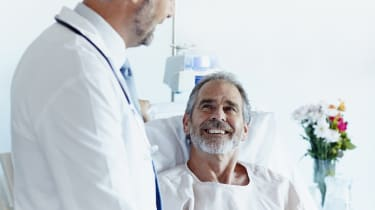 Happy mature patient looking at male doctor in hospital ward