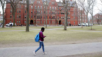 A lone college student walks an otherwise empty college street