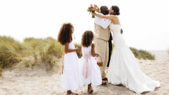 A couple with young children get remarried on a beach
