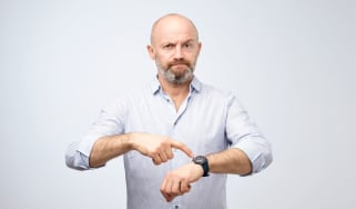 picture of impatient man pointing at his watch