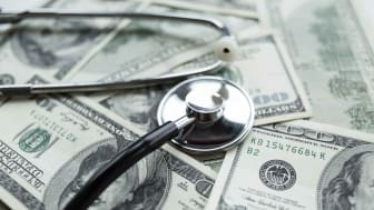A stethoscope on a stack of cash