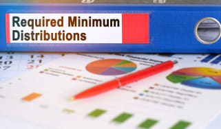 A binder with required minimum distributions written on the side sitting on top of some charts.