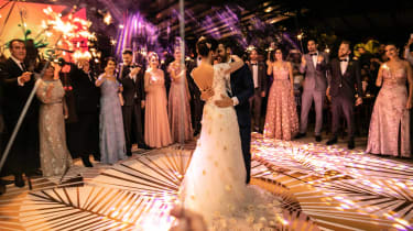 Wedding guests celebrate a newly married couple's first dance