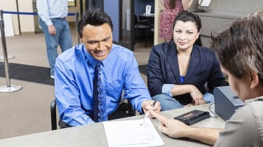 A mature couple receives an application at a bank.