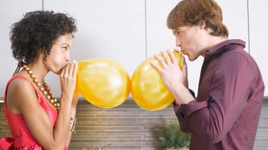 A man and a woman blow up balloons.