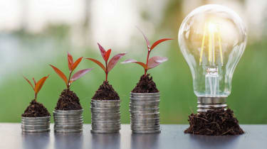 plant growing on coins and light bulb. concept saving money