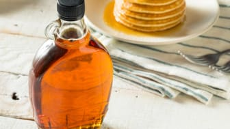 A bottle of maple syrup on a breakfast table