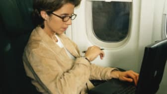Businesswoman working on laptop in airplane