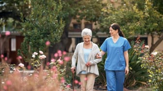 A nurse helps a woman at a nursing home.