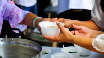 picture of a person handing out bowls of soup