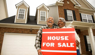 A couple stands outside of their house with a for sale sign