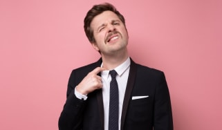 A man grimaces as he pulls a too-tight dress shirt collar away from his neck.