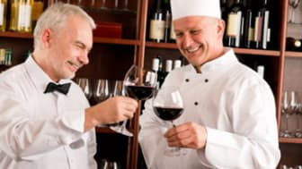 Chef cook and waiter wine tasting restaurant