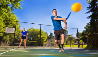 A young man and woman play pickleball as a team.