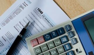 picture of tax forms, a pen, and a calculator