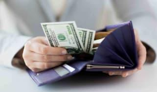 Person putting 100 dollar bills in their wallet