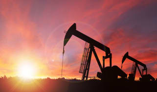 Pump jack silhouette against a sunset sky with deliberate lens flare and copy space. These jacks can extract between 5 to 40 litres of crude oil and water emulsion at each stroke.This image i