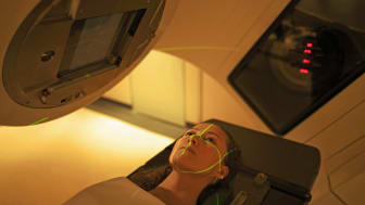 Lasers aligning over the body of a woman undergoing radiation treatment.