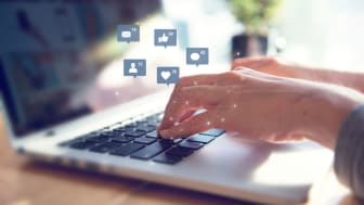 hands on laptop with social media icons popping up