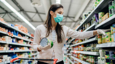 A woman with a mask shops in a grocery store.