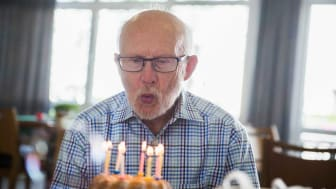 picture of elderly man blowing out candles on a birthday cake