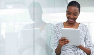 Young business woman in an office looking at an iPad and smiling.