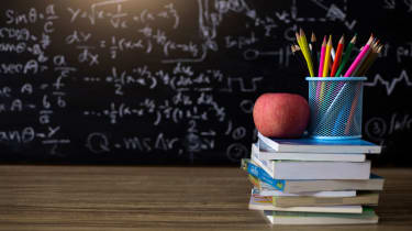 picture of books, pencils and an apple on a teacher's desk