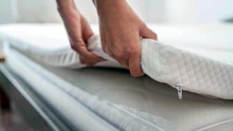 A person lifts up part of a mattress