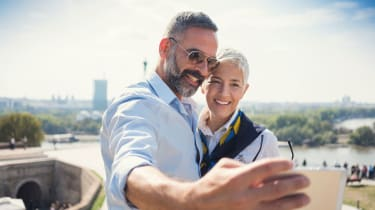 Traveling middle-age couple take a rooftop selfie