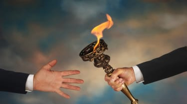 Businessman's outstretched arm passing a flaming torch to another businessman's open hand