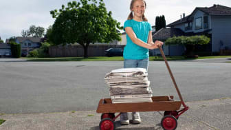 Girl pulling a wagon with newspapers